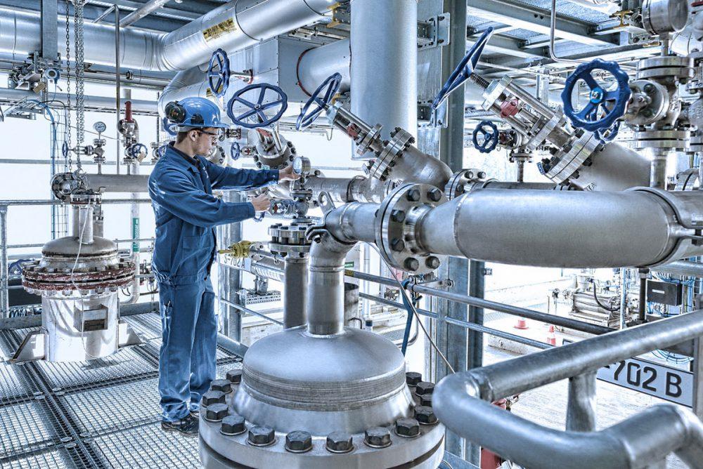 Arbeiter prueft Druck an Industrieanlage