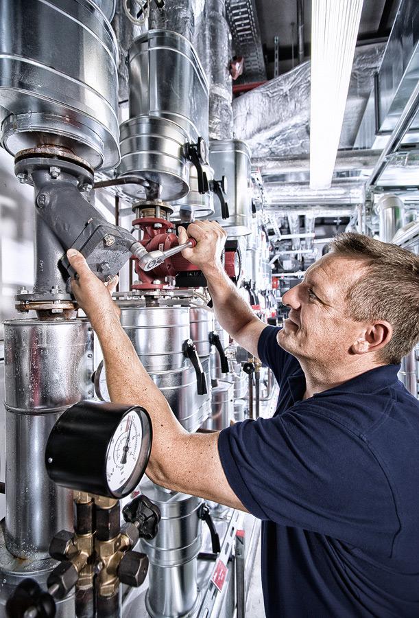 Mitarbeiter repariert Bauteil eines Klimasystems