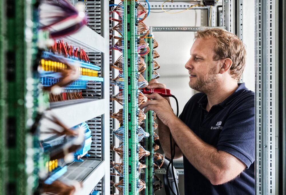 Mitarbeiter überprüft Komponenten in Schaltschrank