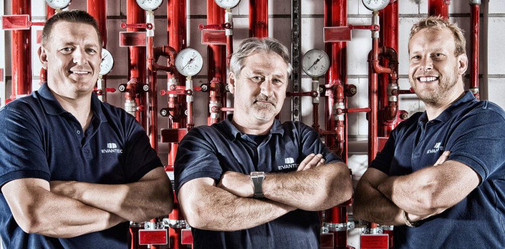 Portraitaufnahme von 3 Mitarbeitern vor Rohrleitungssystem