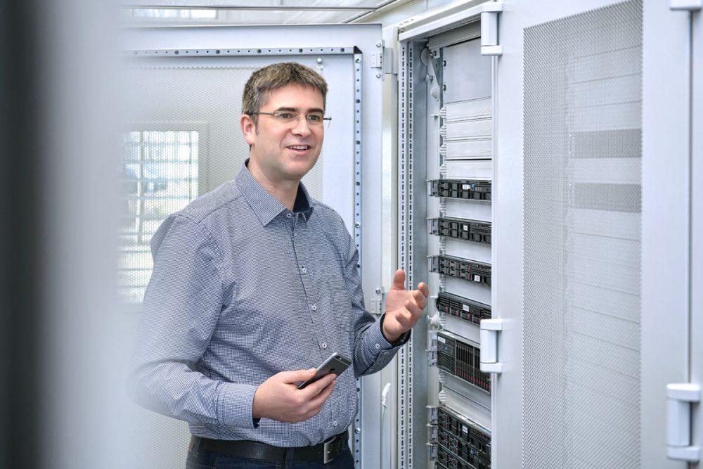 Mitarbeiter im Serverraum im Gespraech