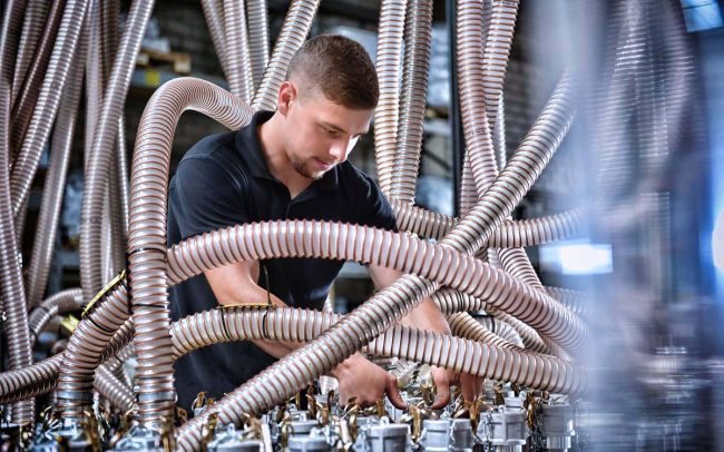 Arbeiter prueft Anschluesse einer Industrieanlage